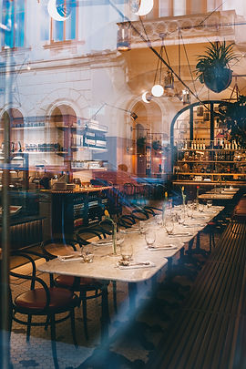 Restaurant design with long table setting and wine glasses.