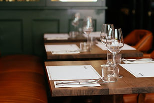 Table setting with wine glasses and menus in a restaurant