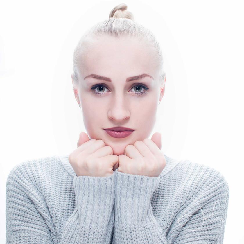 High key portrait of blonde woman in grey jumper. Studio portrait.