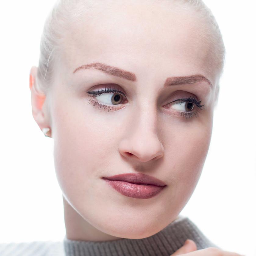 High key headshot of blonde woman. White background.
