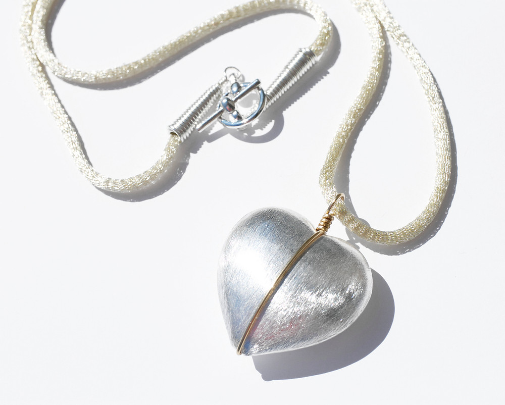 Large silver coloured statement heart pendant