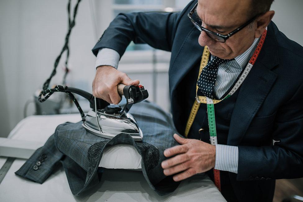 Tailleur de costume sur mesure en train de repasser un col de veste sur mesure