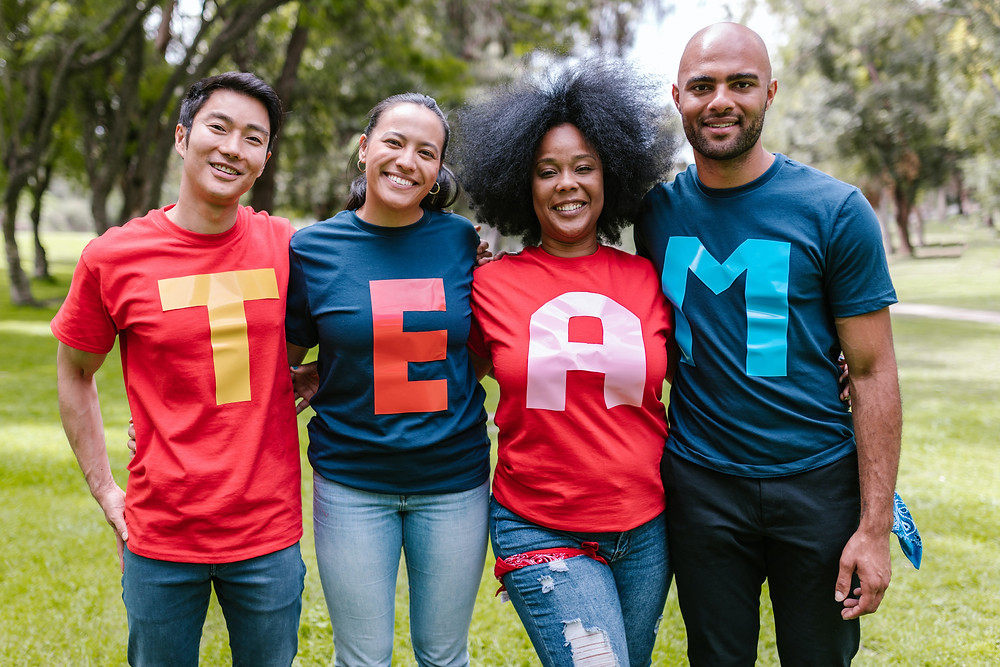 four people wearing t shirts which spell out team