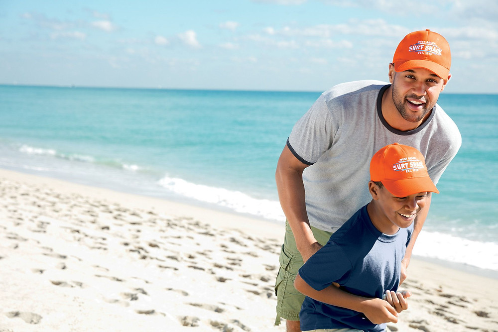 father and son wearing hats on the beach