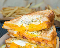 A cage-free egg nestled in our Three Cheese Classic