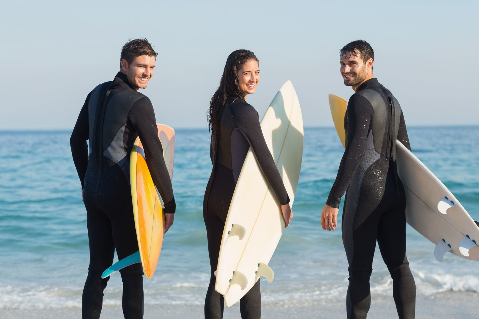 two-men-one-woman-surfboards-wetsuits