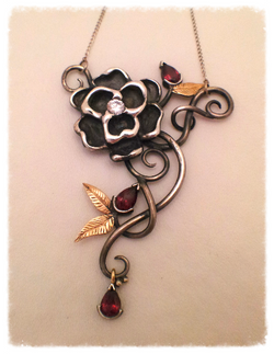 Silver floral pendant with garnets