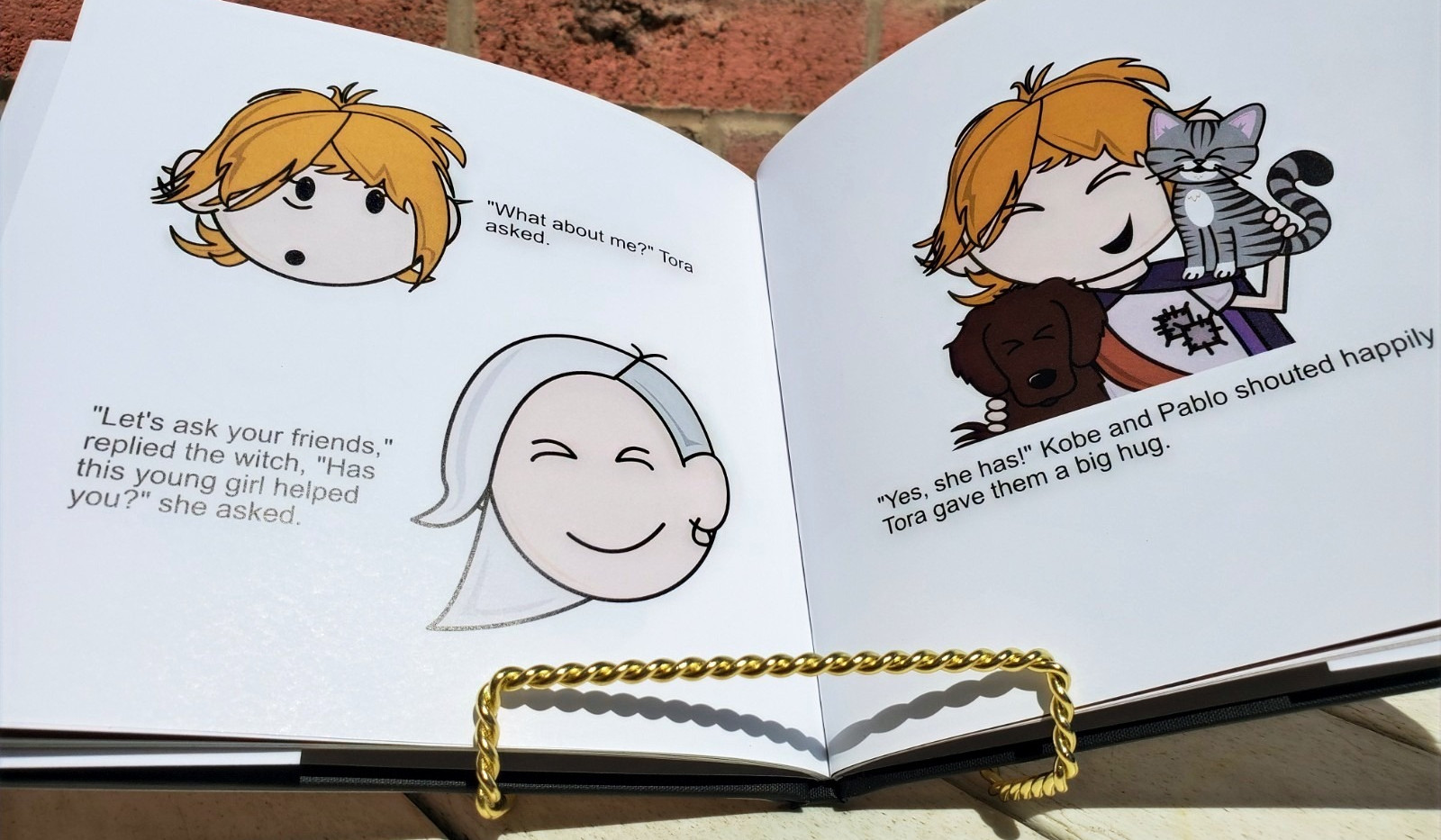 The custom female version of the storybook is open with pictures of the main femal character and a dog and cat.