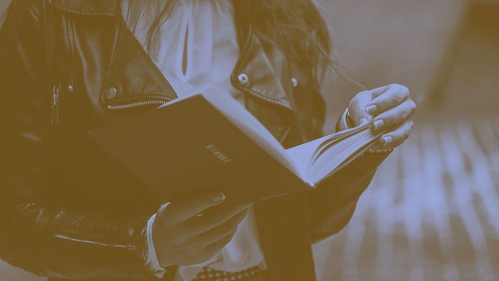 6 Dicas para usar a Leitura em Inglês para Fixar Gramática e Ampliar Vocabulário garota livro leitura lendo aulas particulares de ingles jaqueta jeans preta caderno