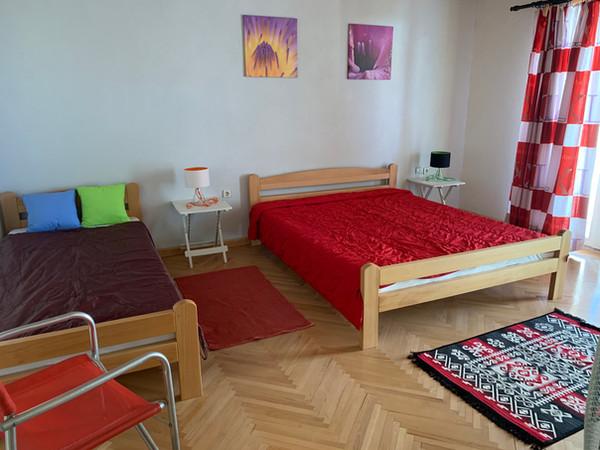 Kamer boven met tweepersoonbed en eenpersoonsbed, openslaande deuren naar terras