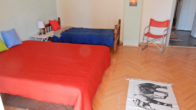 Kamer  boven met tweepersoonsbed en 2 eenpersoonsbedden, openslaande deuren naar terras