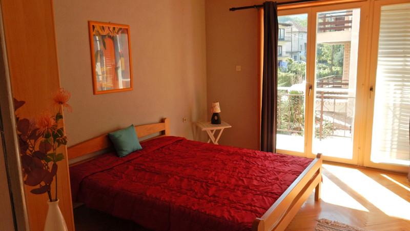 Kamer boven met tweepersoonsbed, openslaande deuren naar terras