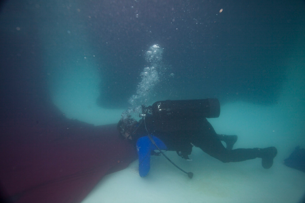Matt McGee repositions a backdrop during an underwater fashion photo shoot
