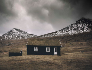 Grass roof house and mountains near the village Gjov in the Faroe Islands