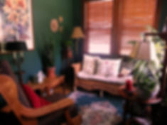 Picture of Arlyn's coaching room. Dark green walls with wooden rocker facing love seat with pillows.