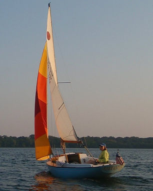 Arlyn sailing her boat, Freelance in the golden time of day.