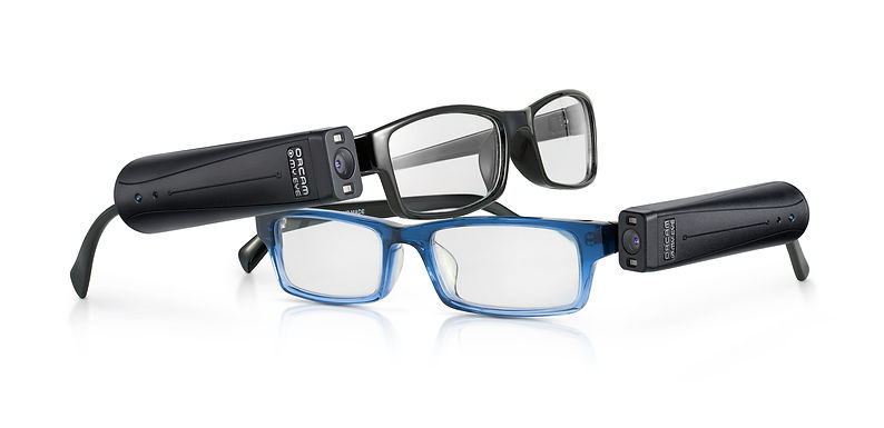 2 pairs of eyeglasses. One black the other blue. Each has an Orcam myeye device attached to the frame near the temples