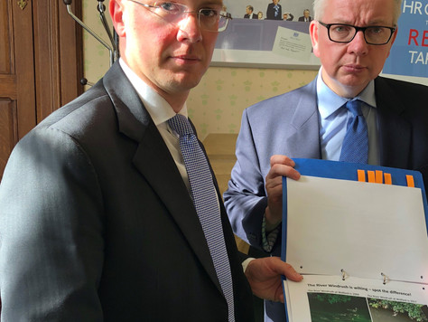 Environment Minister with the Windrush Against Sewage Pollution photos in his hand.