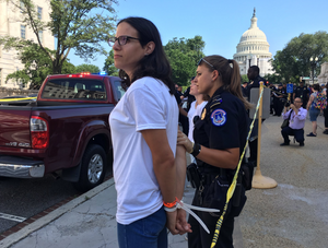 Rebecca, arms behind her back and secured with zip ties, with the Capitol Building in the background