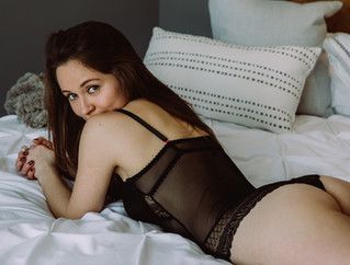 bride to be in black lingerie lays on bed while showing off booty