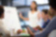 Blurred photo of meeting room. Woman standing at easel. Men and women are sitting around table with papers, folders, tablets, coffee.