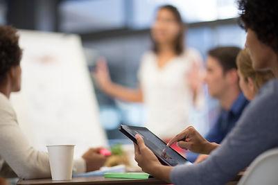 Mulher digita tablet durane reunião