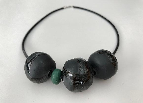 Black clay beads with green glaze drip