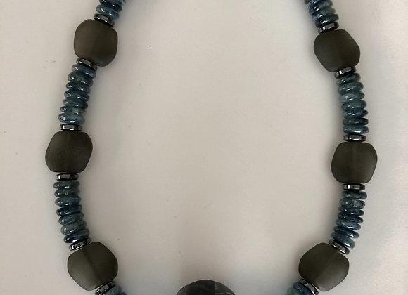 Raku fired ceramic bead with metallic glaze and kyanite