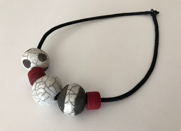 Raku fired ceramic beads with red resin on woven cord