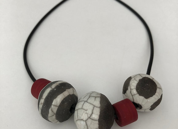 Raku fired ceramic beads with red resin on rubber cord