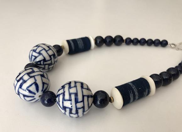 Indigo and white porcelain, lapis, and bone with Japanese Kasuri fabric