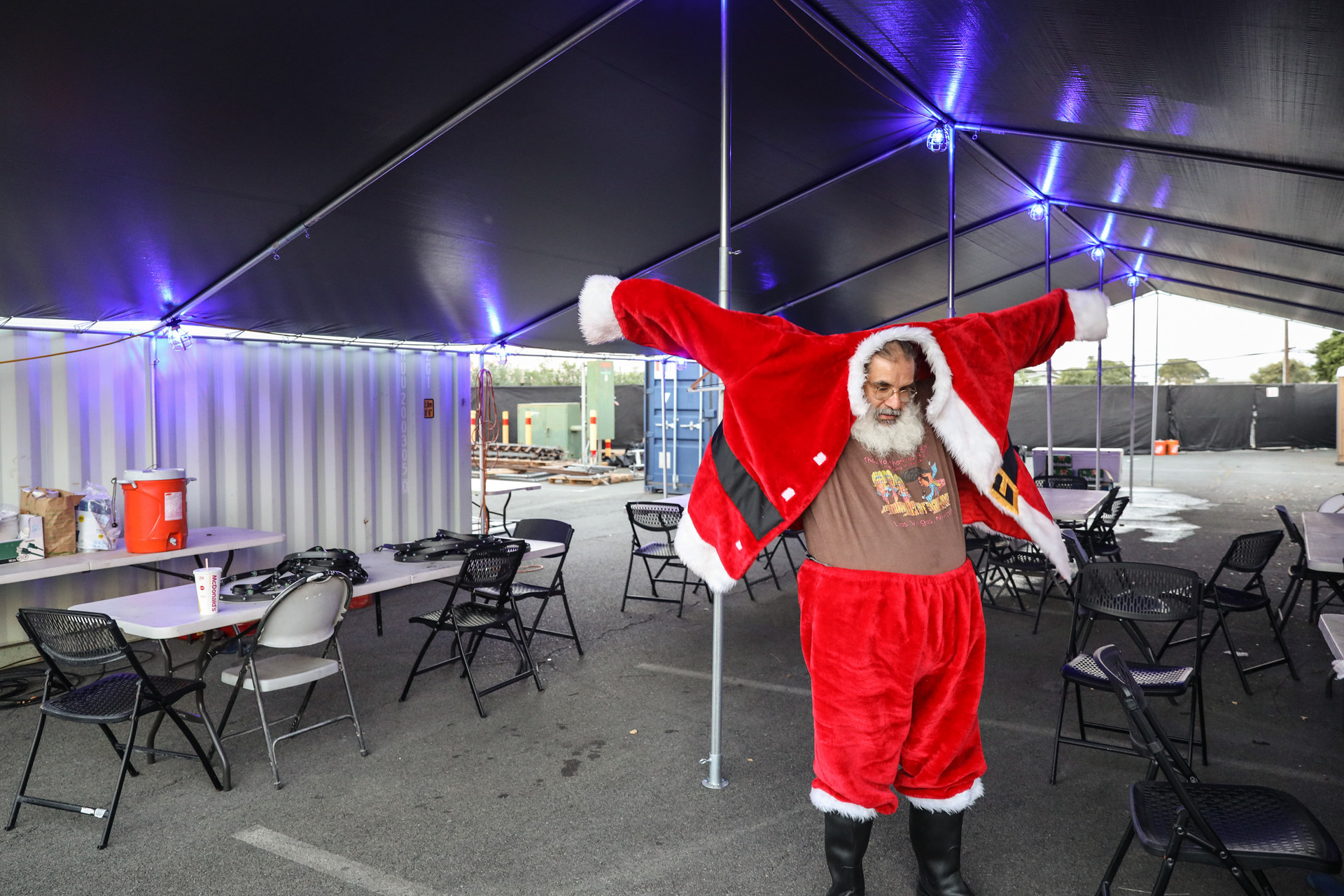 When the clock hits 5:30 in the evening, Don Gonzales starts putting on his Santa outfit backstage of the Christmas light show.