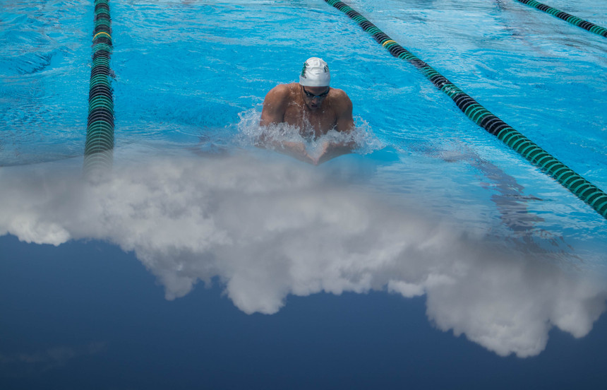 Clouds are reflected while a University of Hawaii swimmer dives during a swim meet between University of Hawaii at Manoa Swimming team and Minnesota Swimming and Diving team on January 12, 2019 (Not a double exposure or manipulation).