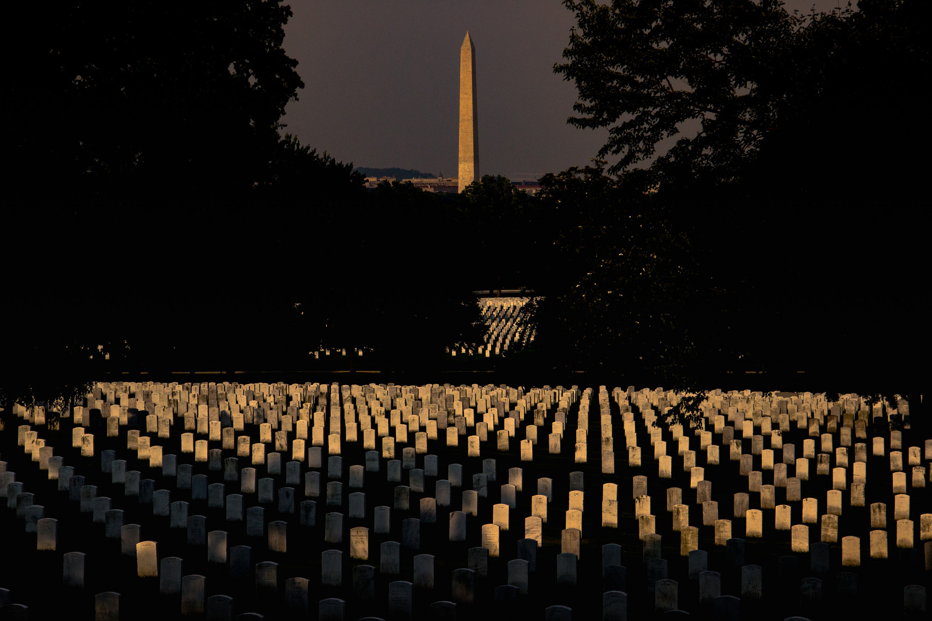 The light from the settign sun streams on the headstones of the unknown fallen soldiers and the Washington Monument at the Arlington National Cemetery on June 18, 2018.