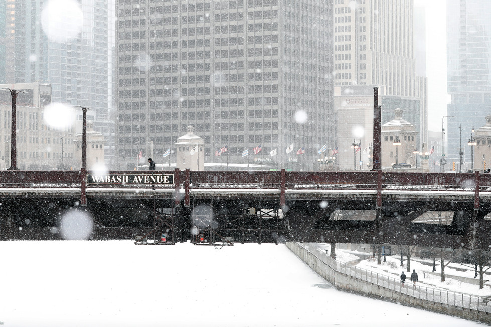 A lone person walks over the Wabash Avenue bridge as others make their way down the icy River Walk on Monday, Feb. 8, 2021, in Chicago during a snow storm. The Greater Chicago area is expected to experience an arctic air mass leading to a subzero temperature. (AP Photo/Shafkat Anowar)