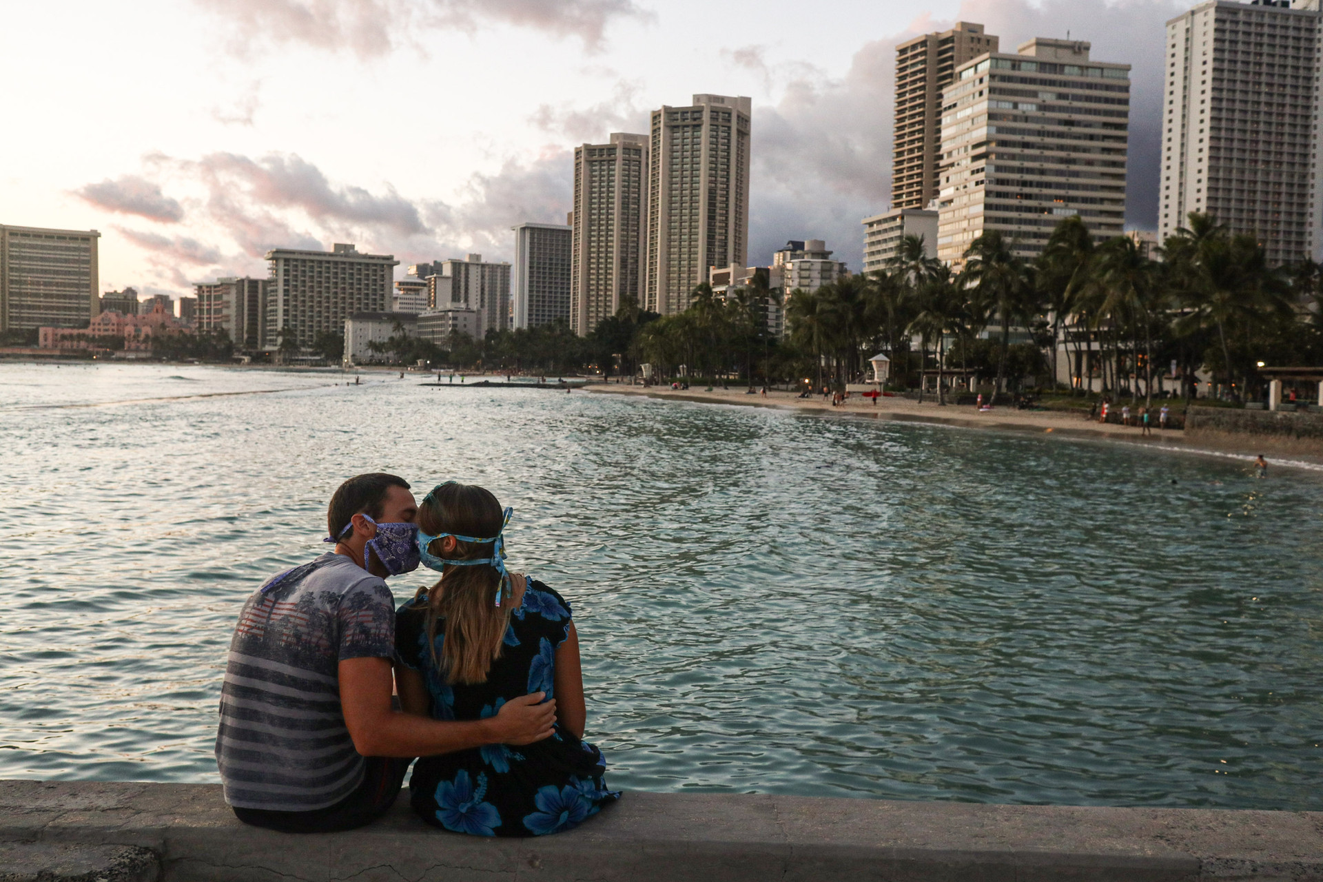 A couple spends some time close to each other in Waikiki beach on April 10, 2020. During a typical summer time, this beach is supposed to be flooded with beach goers but upon restricting the incoming tourists with 14-day mandatory quarantine, the number has dropped significantly.