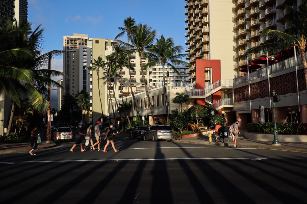 People wearing mask cross the road at Waikiki, Honolulu on November 20, 2020.