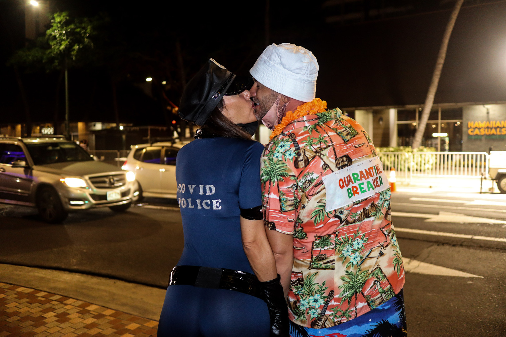 "Visitors dressed as ""Covid Police"" and Quarantine Breaker"" on the Waikiki street on Halloween night, October 31, 2020. Every year on Halloween, Waikīkī sees a record number of people flooding the streets in the wildest of costumes migrating from one bar to another. It is thought to be the busiest night of the year. Not surprisingly, Waikīkī saw its fewest number of people compared to past Halloween nights. Although people were seen wearing face masks, some continued to gather in large groups. Honolulu police officers patrolled Waikīkī, encouraging residents and visitors to follow COVID-19 restrictions by enforcing facial coverings and dispersing large groups of people. Sidewalks and parts of beach entrances were barricaded on Kalakaua Avenue to prevent street parking and gathering."