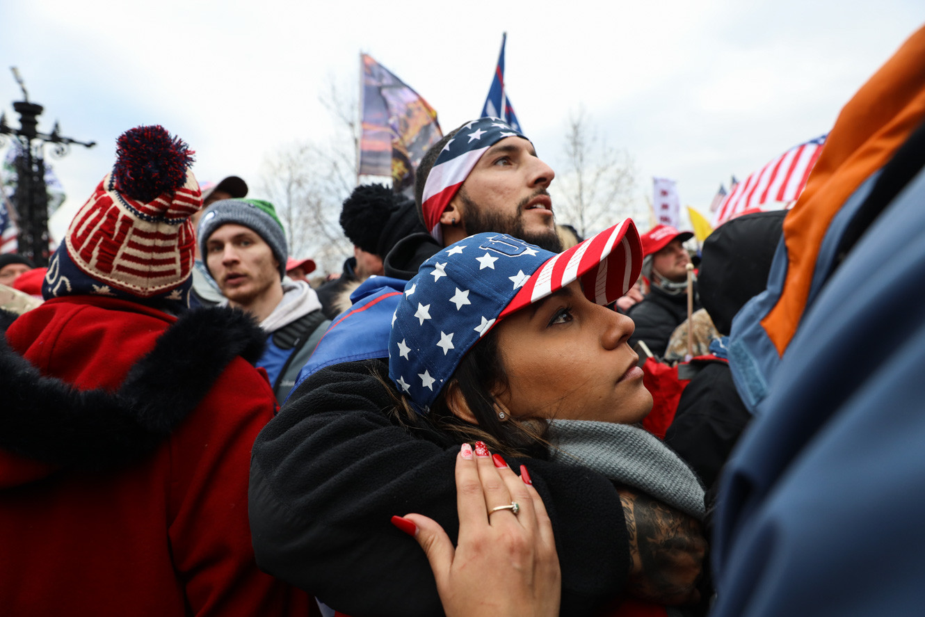 Two supporters hug while thousands of people gathered on the stairs of US Capitol on January 6, 2021. Previously Trump supporters broke through the police barricades to enter the main entrance.