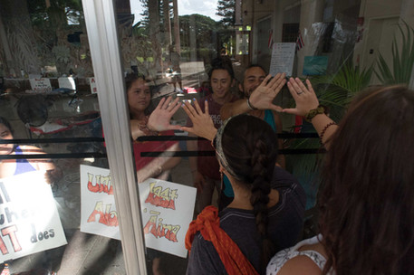 """On October 12, 2019, Mauna Kea kia'i (protectors) at Bachman Hall made the decision to stay locked inside of the building until Monday morning. The kia'i are claiming that the university is trying to """"smoke them out"""" since WiFi in the building has also been cut off on the weekend."""