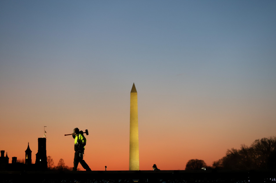 A construction worker carries a hammer on his shoulder on Wednesday, Jan. 13, 2021 at the National Mall in Washington, as a stage is prepared for the 2021 Democrat Joe Biden's presidential inauguration. (AP Photo/Shafkat Anowar)