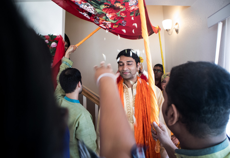 """The bride and groom come downstairs to attend the """"Gaye Holud"""" ceremony while they are welcomed by the guests of the evening."""