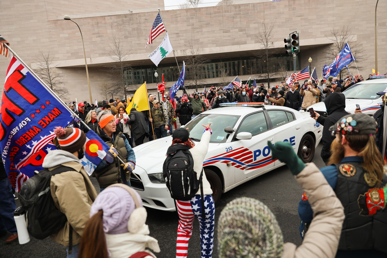Supporters of President Donald Trump block police cars near the U.S. Capitol, Wednesday, Jan. 6, 2021, in Washington. AP Photo/Shafkat Anowar). After primary stage of the Capitol breach more police forces were called to resist people from going up the staircase. Protestors in the mean time found the opportunity to prevent the incoming cars entering the Capitol.