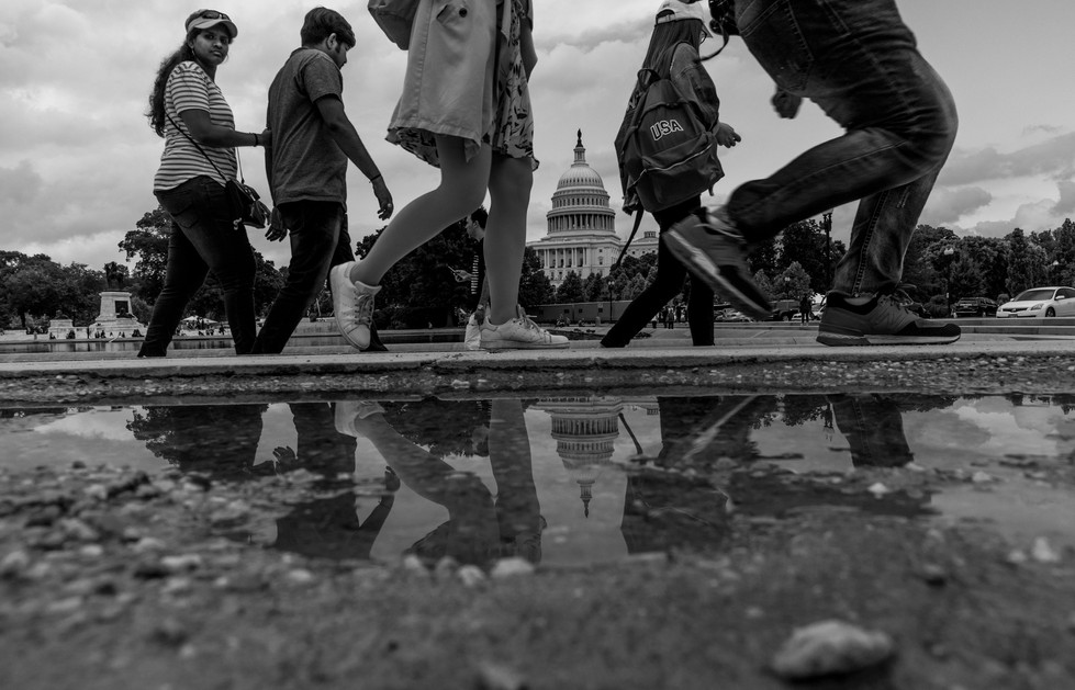 Visitors takes a stroll near the reflecting pool as the U.S Capitol building is refelcted on a stagnant water on June 24, 2018.