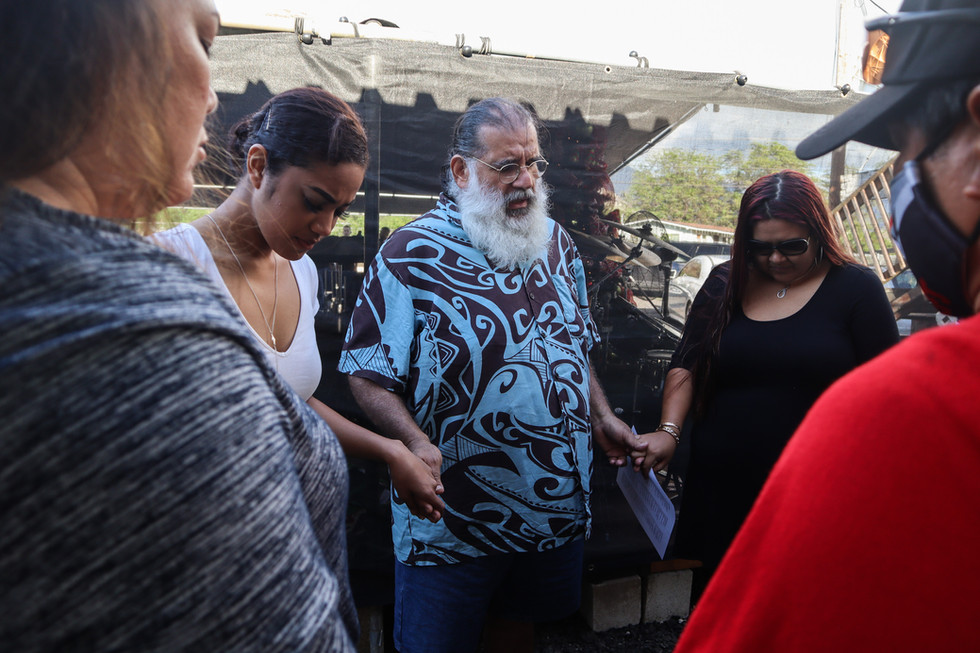 """Back stage, Gonzales prays with his only daughter Shanenalynn and his other band member before the evening mass at a local church in Waianae, HI on December 6, 2020. """"I never wanted my children to see me in that shape because I was a totally different person,"""" said Gonzales about his final effort to give up drugs and alcohol."""