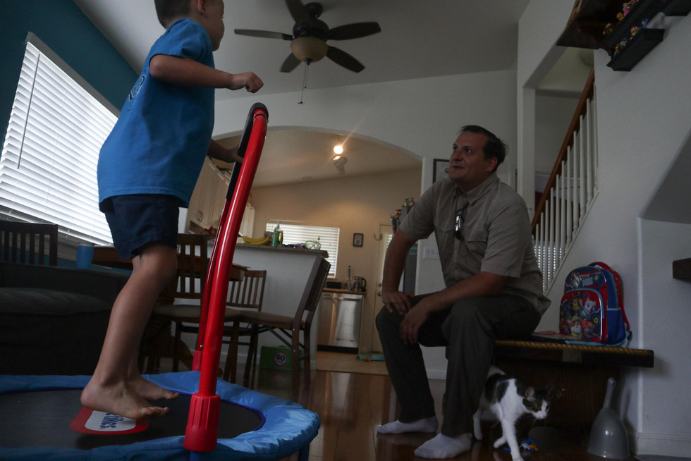 Calvin jumps on the trampoline in the living room while Stremel talks to him.