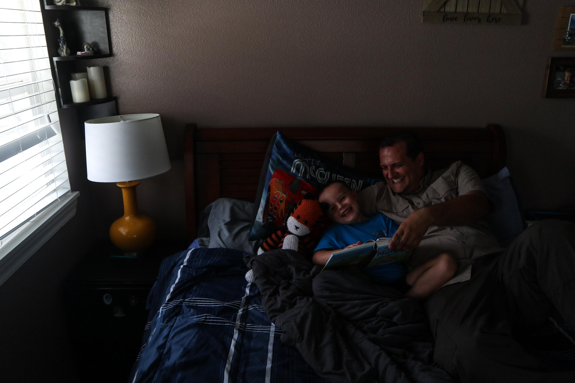 Father and son shares a moment while reading bed time stories in Stremel's bedroom.