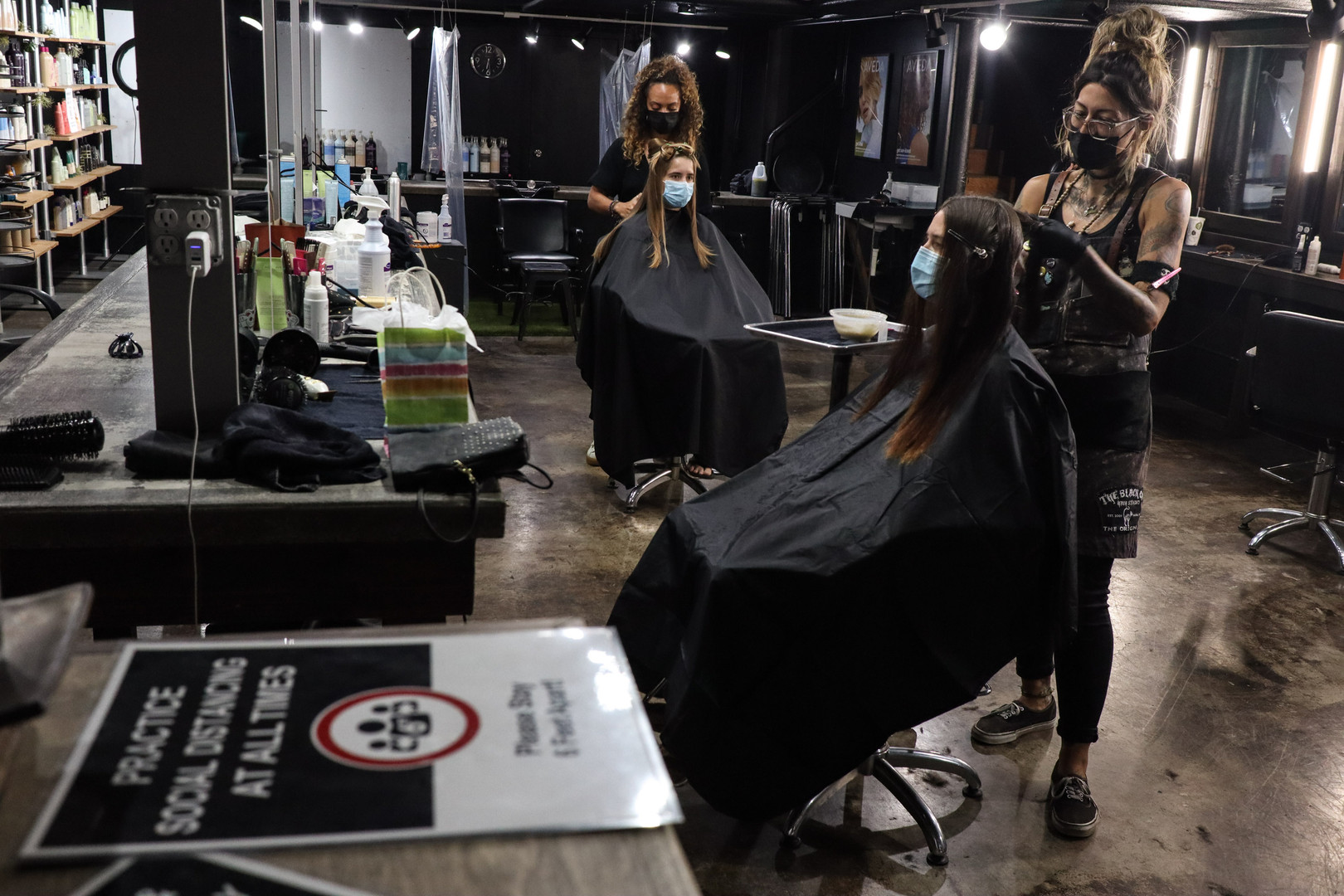 The Black Cat Salon + Spa barbers work inside the salon maintaining social distancing on October 17, 2020. After O'ahu saw new COVID-19 relatively low infection rate, the city eased more restrictions on businesses and activities Thursday, October 22, 2020.