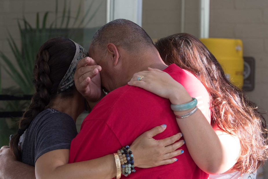 Community member Steven Thomas (middle), Michelle Makalua-yee (left) and University of Hawai'i undergrad student Kameleopu'uwai share an emotional moment with the Maunakea kia'i (protectors) locked inside of Bachman Hall on October 12, 2019.