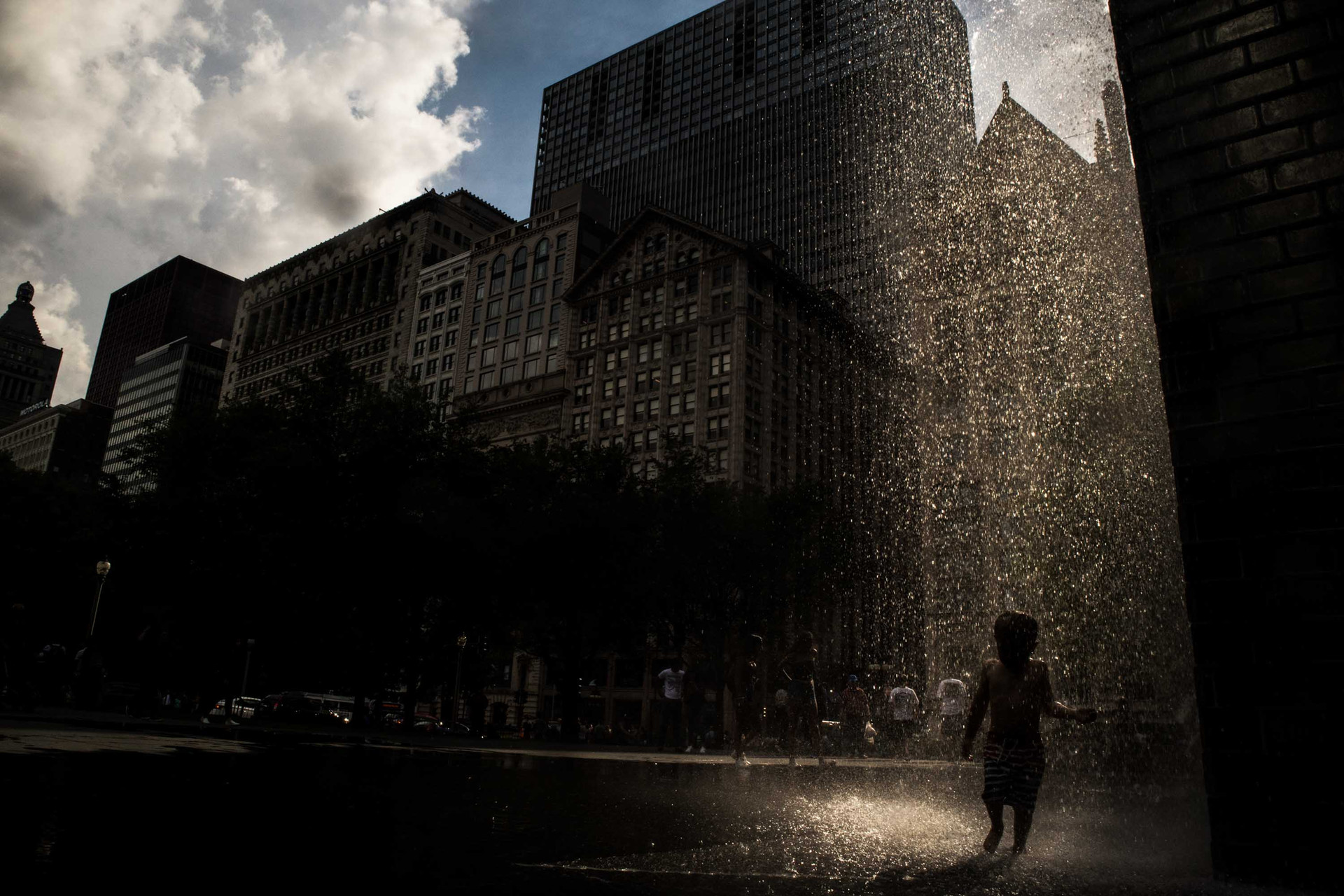 A boy cools himself from the summer heat by the Crown Fountain in Chicago, IL on August 2, 2018.